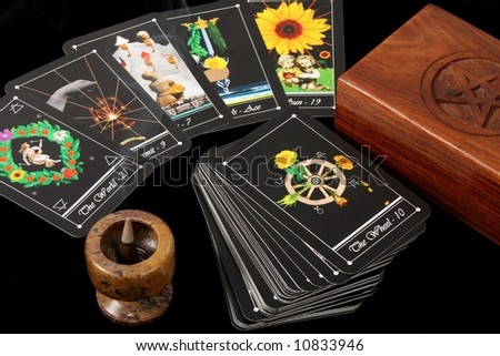 deck of tarot cards spread on table, with crystal, flower and incense burner