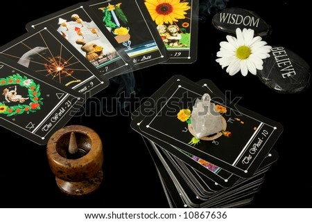 deck of tarot cards spread on table with crystal flower and incense burner