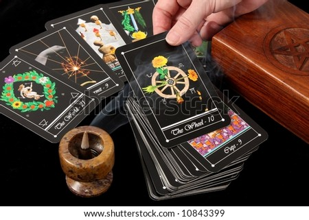deck of tarot cards spread on table with wooden box and incense burner - with hand holding card