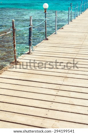 deck pier and a railing on the background of emerald sea