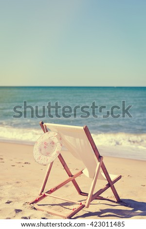 Deckchair and female hat on stunning tropical beach vacation background. Happy time on  holiday location - stock photo