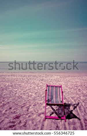 Deckchair, chair on the beach in sunshine day. Empty colorful wooden beach chair on tropical beach with blue sky background in vintage retro tone. To represent the meaning of summer vacation time.