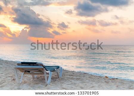 Deckchair on the Caribbean Sea at sunrise, Mexico - stock photo