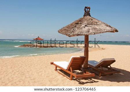 Deckchairs and parasol on the sand beach - stock photo