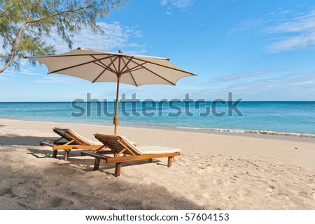 Deckchairs and parasol on the white sand beach facing the lagoon - stock photo