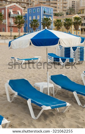 Deckchairs and sunshades on a Costa Blanca beach resort, Spain - stock photo