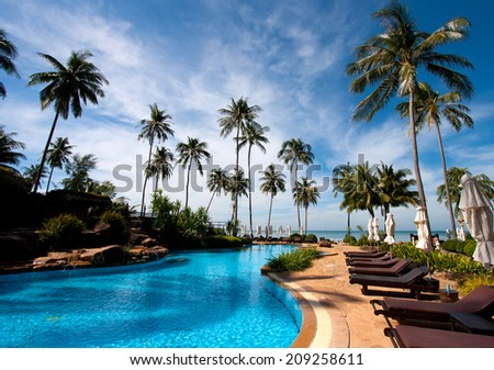 Deckchairs in tropical resort hotel pool - stock photo