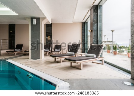deckchairs near indoors swimming pool - stock photo