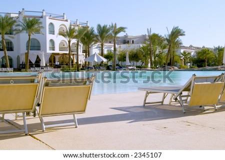 Deckchairs near the swimming pool - stock photo