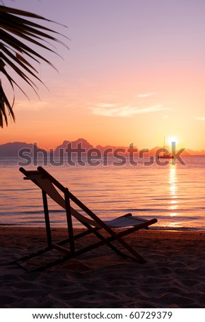 deckchairs on beach at sunset