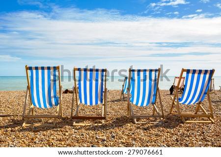 Deckchairs on Brighton beach. Brighton, East Sussex, England - stock photo