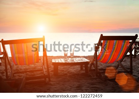 Deckchairs on the beach at sunset - stock photo