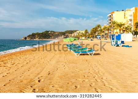 Deckchairs on the beach of Lloret de Mar in the early morning. - stock photo