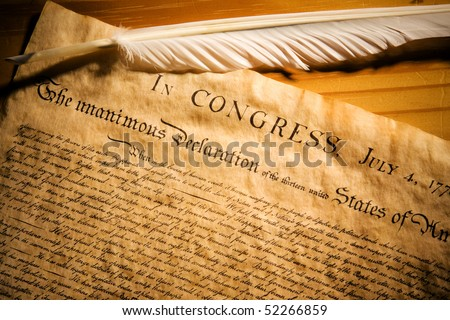 Declaration of Independence with feather quill on wood surface - stock photo