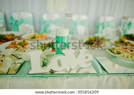 Decor word love on mirror and candle on wedding table - stock photo