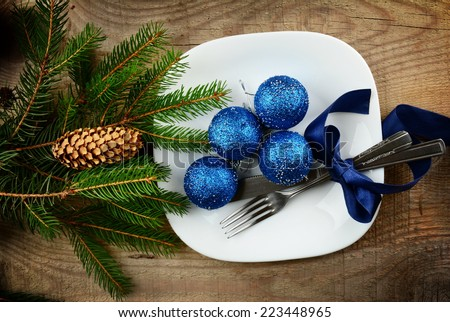 Decorate christmas plate with blue baubles and pines on wooden surface - stock photo