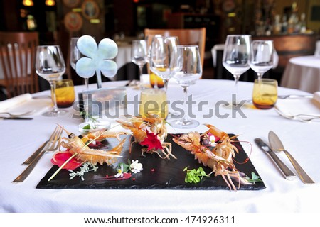Decorated and adorned black dish with prawns on a restaurant table with flower decorations. There is a plate ( space ) where you can enter text.