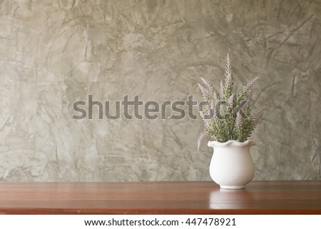 Decorated artificial flowers in flowerpot on wooden table with cement wall background.copy space for text.