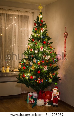 Decorated beautiful Christmas tree with Santa and gifts in interior of the house - stock photo