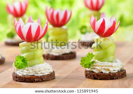 Decorated cheese appetizers: Spiced cream cheese with spiral cucumber and radishes blossoms on pumpernickel - stock photo