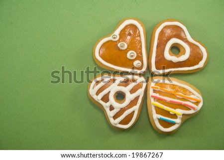 Decorated Christmas cookies in clover formation against green background ad space on left - stock photo