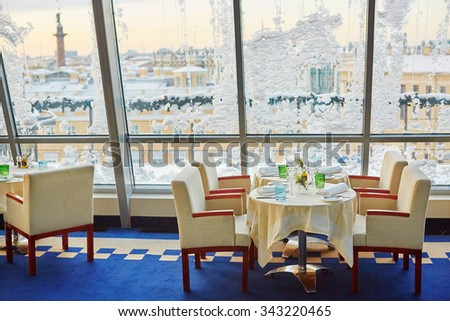 Decorated christmas dining table with wine glasses near the window covered with snow - stock photo