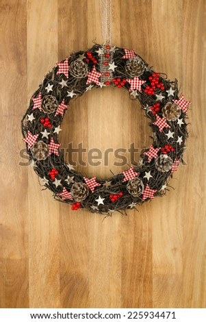 Decorated christmas door wreath with gingham stars and pine cones brown twigs on sapele wood background, copy space - stock photo