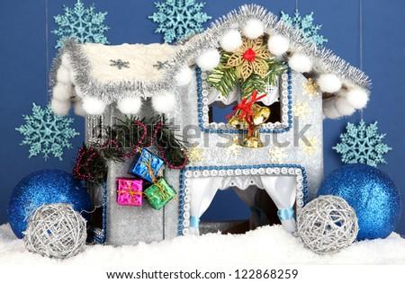Decorated Christmas house on blue background - stock photo