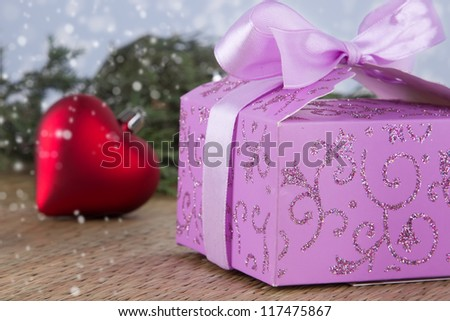 Decorated Christmas purple gift box and red heart with bokeh background