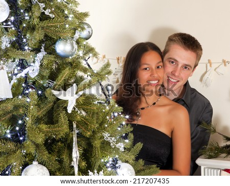 Decorated christmas tree and a young couple of different race - stock photo