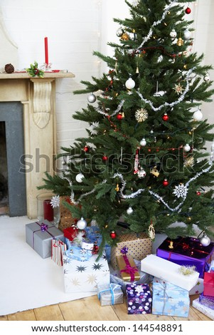 Decorated Christmas tree and gift boxes in living room - stock photo