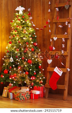 Decorated Christmas tree and ladder on wooden wall background - stock photo