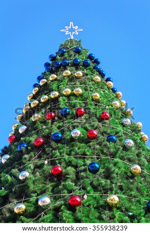 Decorated Christmas tree. Christmas tree against blue sky background - stock photo