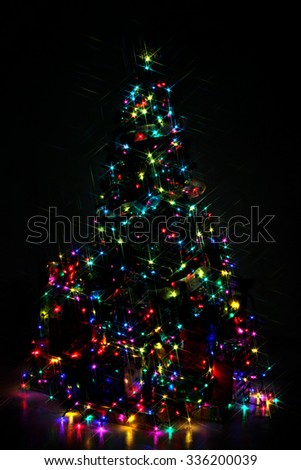Decorated Christmas tree lit up with colorful lights at night - stock photo