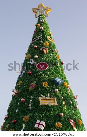 Decorated Christmas tree on blue background - stock photo