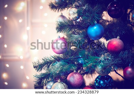 Decorated Christmas tree on blurred backgroun. Blue toned - stock photo