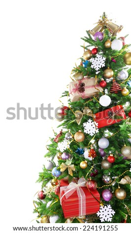 Decorated Christmas tree on floor on light wall background