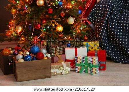 Decorated Christmas tree on home interior background at night - stock photo