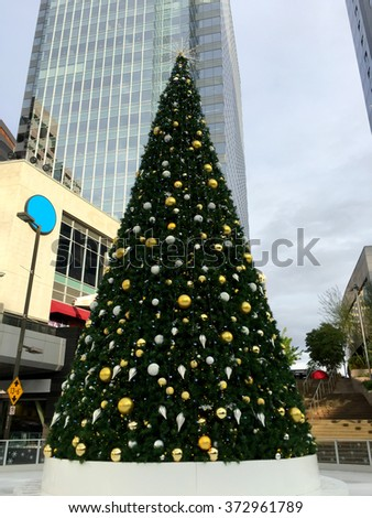 Decorated Christmas tree overshadowed by tall downtown skyscrapers, Phoenix, Arizona - stock photo
