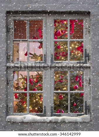 decorated christmas tree seen through and old window with snowfall - stock photo