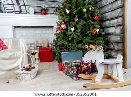 decorated Christmas tree with armchair and fireplace - stock photo