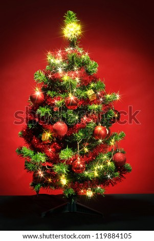 Decorated christmas tree with red balls on red background - stock photo