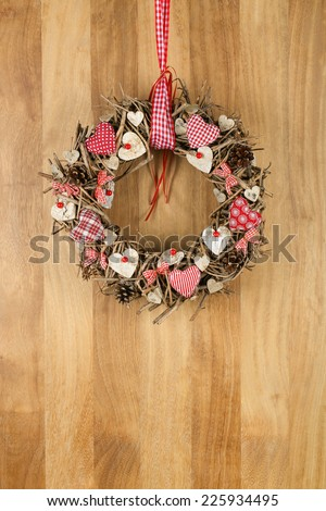 Decorated christmas wreath with red and white pillow hearts brown twigs gingham and polka dot on sapele wood background, copy space - stock photo