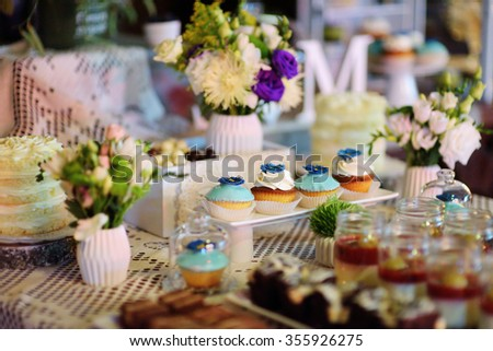 Decorated colorful cupcakes on a dessert table on some festive event - stock photo