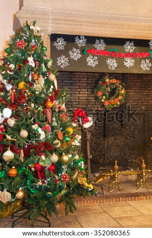 Decorated colorful festive Christmas tree standing on flagstones in front of a large granite hearth with Merry Christmas banner   in a French country house in warm interior light - stock photo