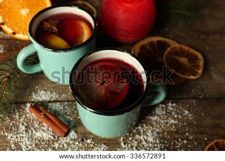 Decorated composition of mulled wine in mugs on wooden table - stock photo