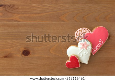 Decorated cookies in the shape of heart on a wooden table - stock photo