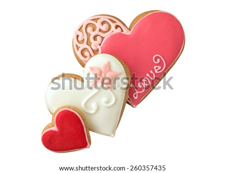 Decorated cookies in the shape of heart on wooden table. Isolated, on white background. - stock photo