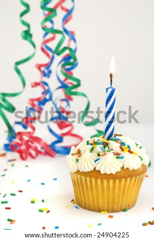 Decorated cupcake with single burning candle with ribbons and sprinkles copy space primary colors