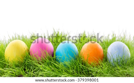 Decorated easter eggs in grass on white background - stock photo